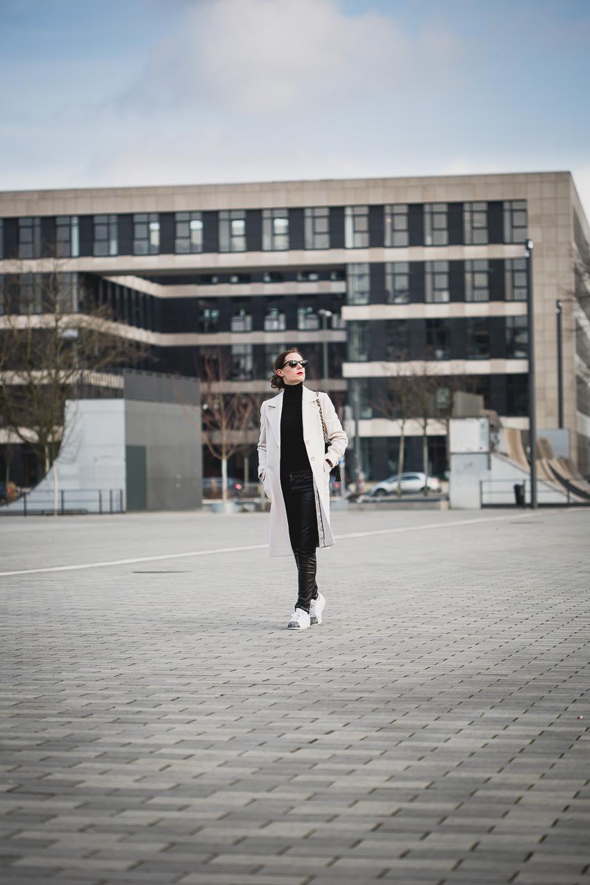 Bürooutfit mit hellem Mantel und Lederhose