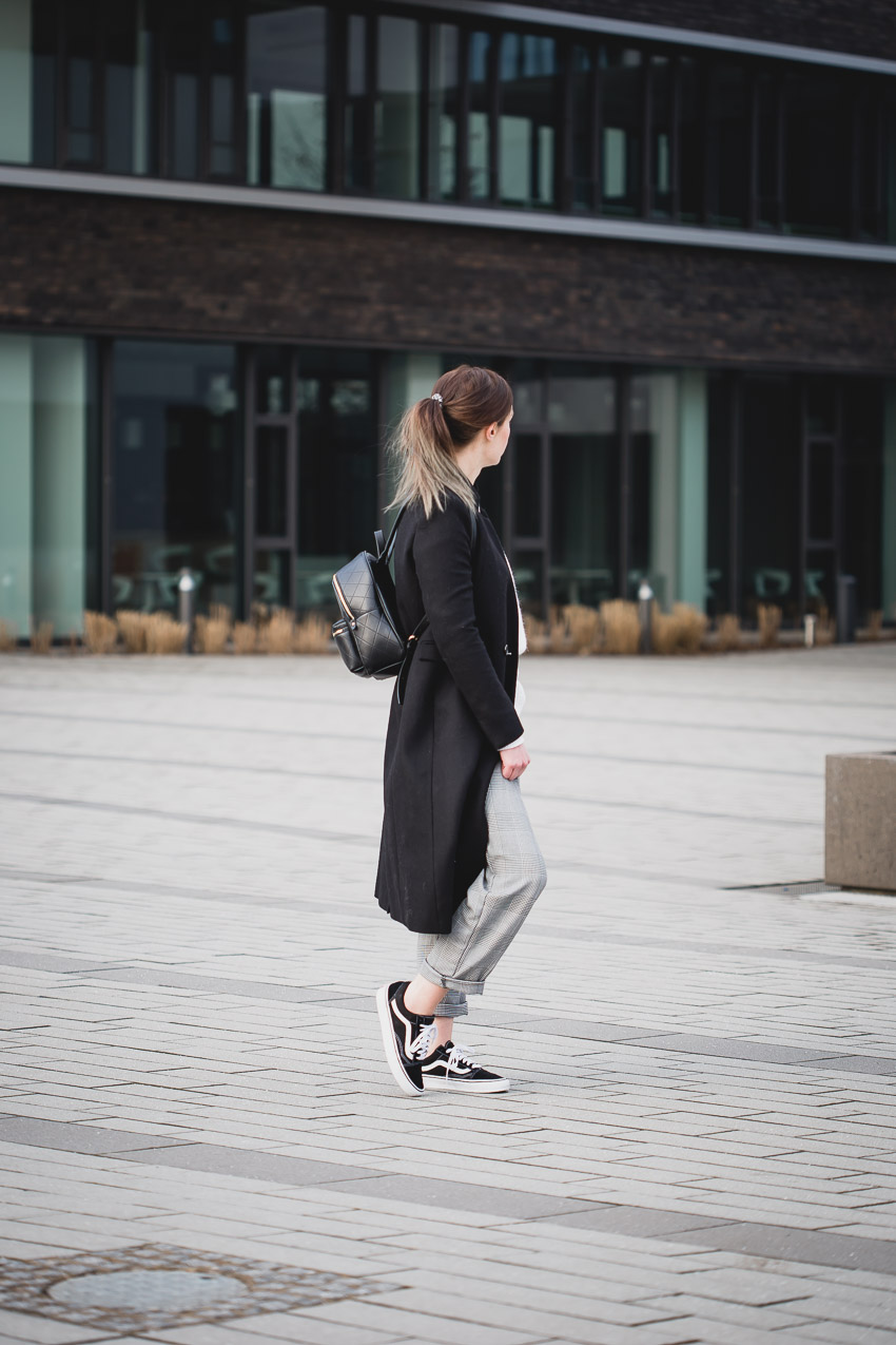 Lässiges Outfit mit schwarzem Mantel und klassischen Vans